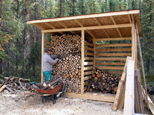 The finished wood shed is filled with firewood from the clear-cut.